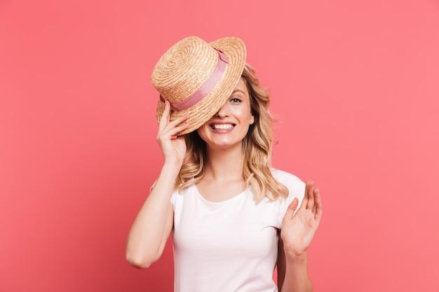 Portret van een trendy blonde vrouw met een strohoed die aan de voorkant glimlacht, geïsoleerd over een roze muur