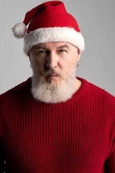 Portret van een trendy man van middelbare leeftijd met een baard met een kerstmuts en een rode trui op zoek
