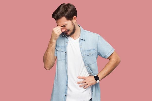 Portret van een trieste alleenstaande, hopeloze bebaarde jongeman in een blauw casual stijlshirt dat staat, zijn hoofd naar beneden houdt en huilt. indoor studio opname, geïsoleerd op roze achtergrond.