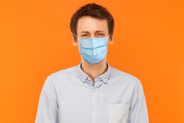Portret van een trieste alleenstaande jonge werknemer met een chirurgisch medisch masker dat staat en naar de camera kijkt met een boos frons gezicht. indoor studio opname geïsoleerd op een oranje achtergrond.