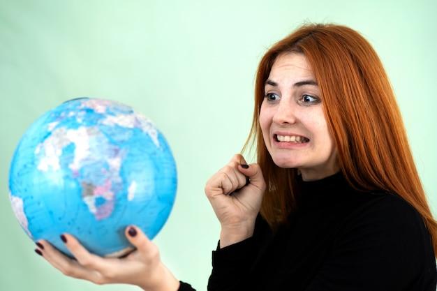 Portret van een trieste bezorgd jonge vrouw die geografische wereldbol in haar handen. reisbestemming en planeetbescherming concept.