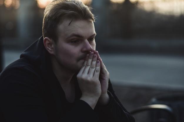 Portret van een trieste en depressieve man die alleen op straat zit
