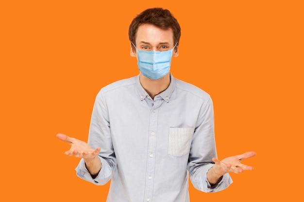 Portret van een trieste, gestresste jonge werknemer met een chirurgisch medisch masker dat staat en naar de camera kijkt met een droevig gezicht en vraagt. indoor studio opname geïsoleerd op een oranje achtergrond.