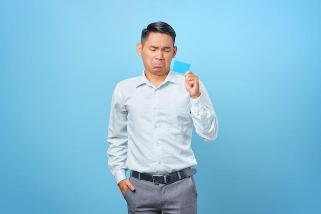 Portret van een trieste jonge knappe zakenman die een creditcard in de hand houdt op blauwe achtergrond