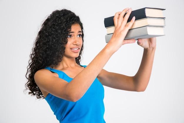 Portret van een trieste jonge vrouw die op veel boeken kijkt die op een witte muur worden geïsoleerd