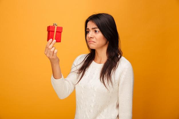 Portret van een trieste jonge vrouw met kleine geschenkverpakking