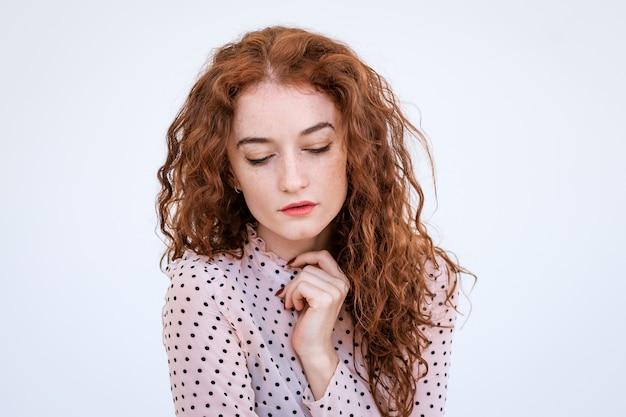 Portret van een trieste jonge vrouw met rood haar close-up, neergeslagen ogen op een lichte achtergrond