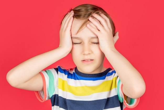 Portret van een trieste jongen die zijn hoofd vasthoudt met zijn hand, geïsoleerd op de rode achtergrond. kleine jongen met hoofdpijn. wanhoop, tragedie