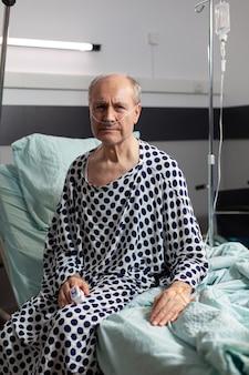 Portret van een trieste, onwel senior man zittend op de rand van het ziekenhuisbed met een infuus eraan bevestigd en ademen met hulp van een zuurstofmasker, kijkend naar de camera.