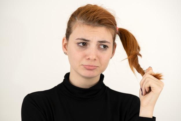 Portret van een trieste roodharige tiener die met kinderachtig kapsel beledigd kijkt
