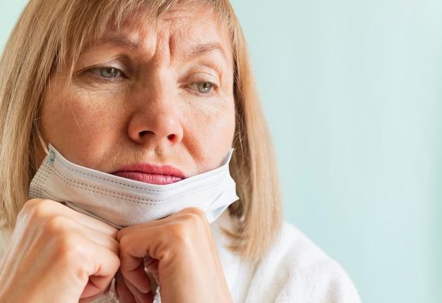 Portret van een trieste vrouw die een medisch masker draagt vanwege de coronavirus-epidemie