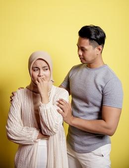 Portret van een trieste vrouw een man kalmeert een vrouw. geduld, alles komt goed. geïsoleerd op gele achtergrond