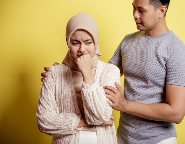 Portret van een trieste vrouw een man kalmeert een vrouw. geduld alles komt goed. geïsoleerd op gele achtergrond