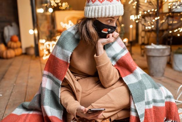 Portret van een trieste vrouw met gezichtsmasker tijdens de nieuwjaarsvakantie thuis op het prachtig versierde terras. concept van quarantaine en zelfisolatie tijdens de epidemie op feestdagen