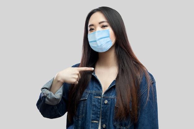 Portret van een trotse tevreden mooie brunette aziatische jonge vrouw met een chirurgisch medisch masker in een blauw spijkerjasje dat naar zichzelf wijst en naar de camera kijkt. studio-opname, geïsoleerd op een grijze achtergrond