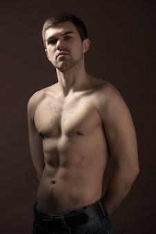 Portret van een trotse zelfverzekerde jonge mannelijke atleet met een mooi figuur en druk op kubussen tegen een donkere muur