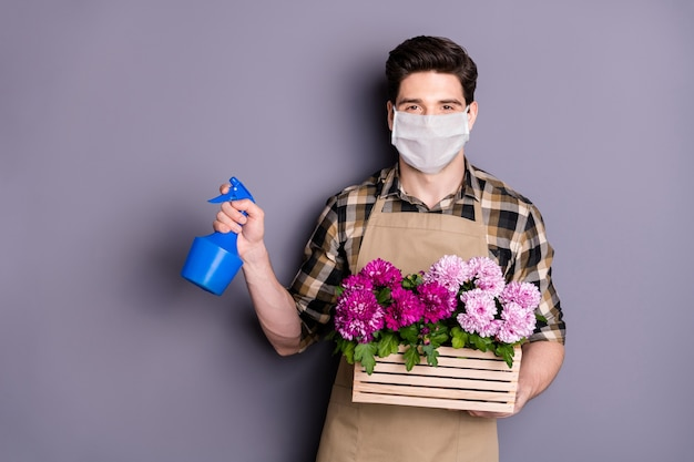 Portret van een tuinman die een veiligheidsmasker draagt, bloemen, pot, waterplanten, stop infectie, cov-ziekte