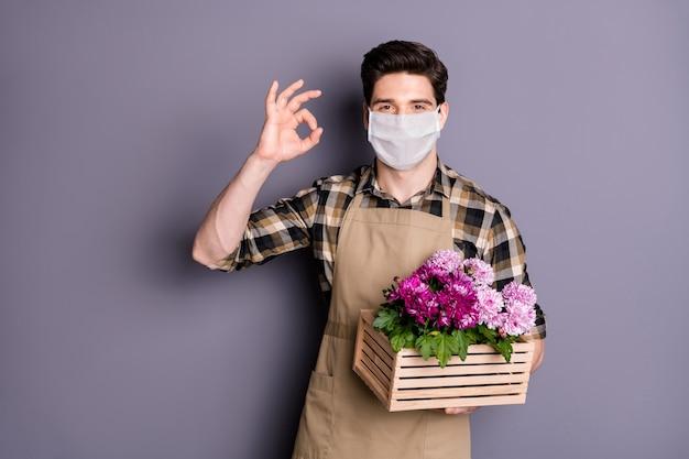 Portret van een tuinman die een veiligheidsmasker draagt, houd bloemen vast, stop infectie, ziekte, toon ok-teken