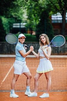 Portret van een twee vrouw die samen buiten tennis speelt.