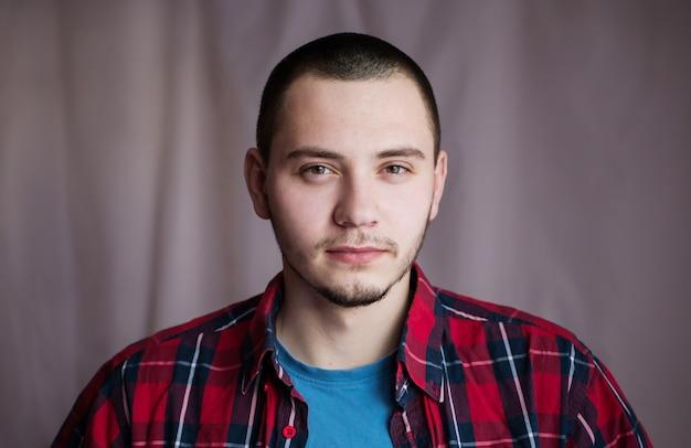 Portret van een twintigjarige man in een blauw overhemd en geruit overhemd met natuurlijk licht