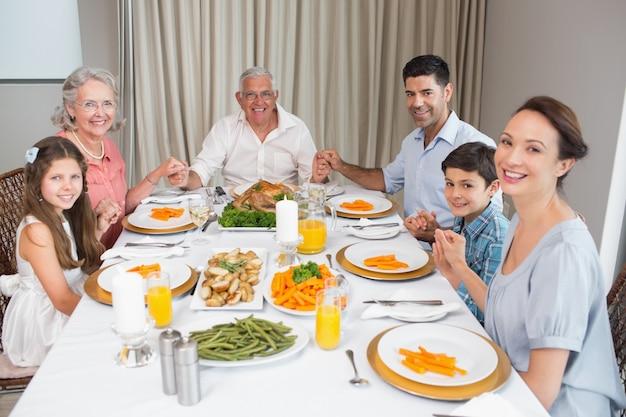 Portret van een uitgebreide familie aan eettafel