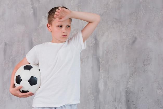 Portret van een uitgeputte bal van het de holdingsvoetbal van de jongen ter beschikking tegen concrete muur
