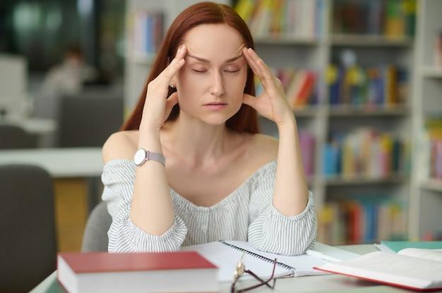 Portret van een uitgeputte donkerharige blanke dame die met haar ogen dicht aan de bibliotheekbalie zit