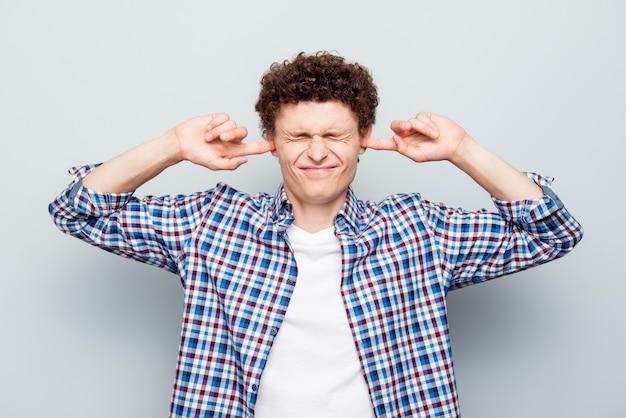 Portret van een uitgeputte man wil geen geluid luisteren dat op grijs wordt geïsoleerd