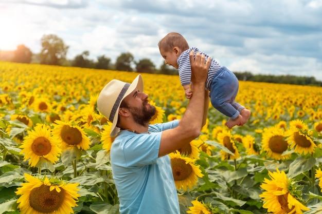 Portret van een vader in een blauw shirt en een strohoed en zijn baby die plezier heeft in een veld met zonnebloemen, zomerse levensstijl