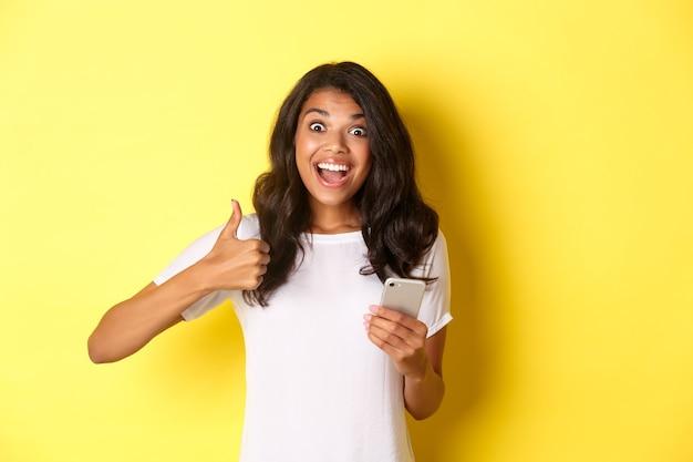 Portret van een verbaasd afrikaans-amerikaans meisje dat thumbsup laat zien en mobiele telefoon gebruikt die coole app-st...