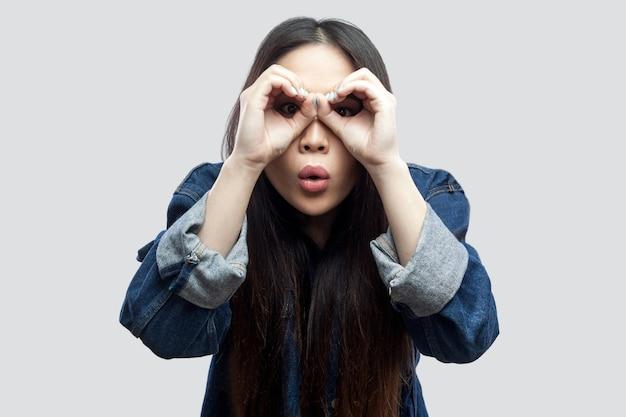 Portret van een verbaasd mooi brunette aziatisch meisje in een casual blauw spijkerjasje met make-up die met een verrekijker handgebaar op de ogen staat en er uitziet. studio opname, geïsoleerd op lichtgrijze achtergrond.