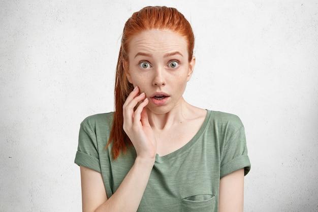 Portret van een verbaasd roodharig vrouwelijk model met een verbaasde uitdrukking, staart met een bange blik terwijl ze zich realiseert dat ze vergat rekeningen te betalen, bang voor iets