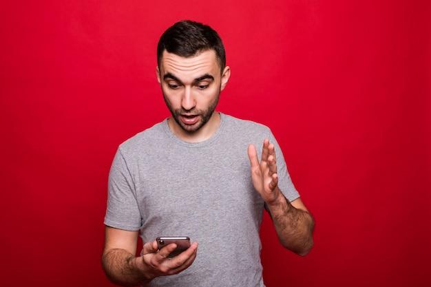 Portret van een verbaasde casual man kijken naar mobiele telefoon geïsoleerd op rode achtergrond