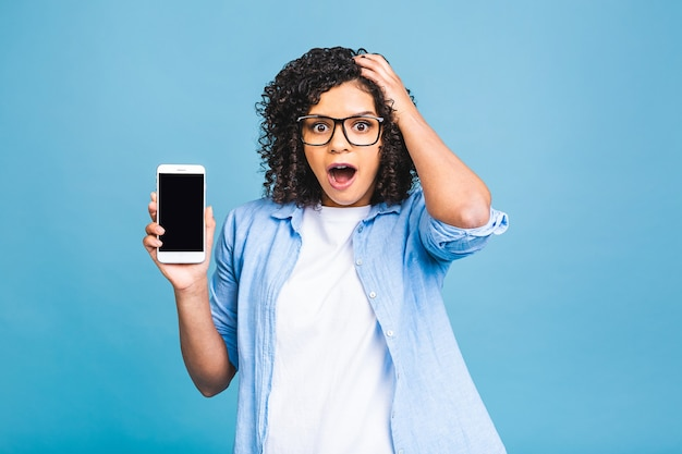 Portret van een verbaasde geschokte jonge afro-amerikaanse zwarte vrouw met leeg scherm mobiele telefoon geïsoleerd op blauwe achtergrond.