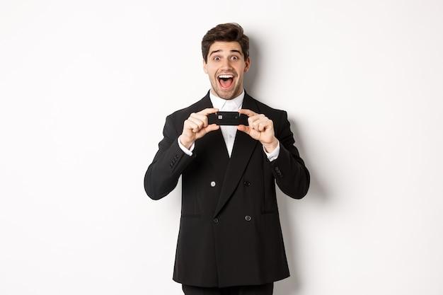 Portret van een verbaasde knappe man in een zwart pak, die een creditcard toont en een bank aanbeveelt, staande op een witte achtergrond