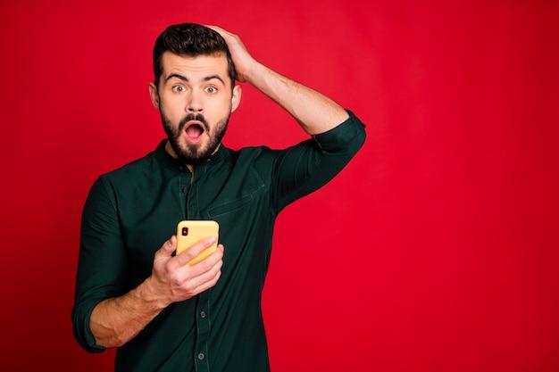 Portret van een verbaasde man gebruik smartphone lees social media nieuws onder de indruk raak zijn hoofd schreeuw draag moderne outfit