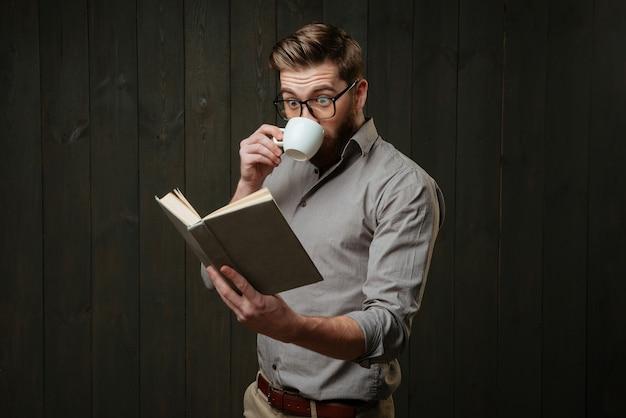 Portret van een verbaasde man met een baard in een bril die koffie drinkt en naar een open boek kijkt dat op een zwart houten oppervlak is geïsoleerd