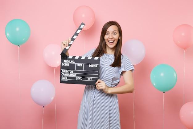 Portret van een verbaasde mooie jonge vrouw die een blauwe jurk draagt met klassieke zwarte film die filmklapper maakt op een roze achtergrond met kleurrijke luchtballonnen. verjaardag vakantie feest mensen oprechte emoties.