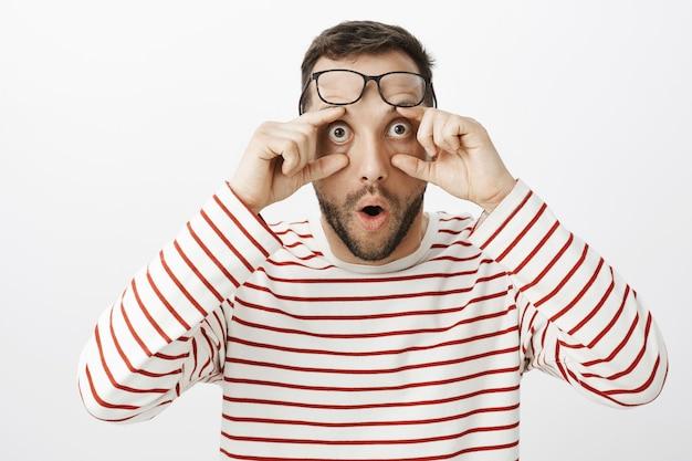 Portret van een verbaasde, verbaasde, grappige mannelijke collega, die een bril op het voorhoofd houdt en aan de oogleden trekt, starend met gepofte ogen naar iets raars en ongelooflijks
