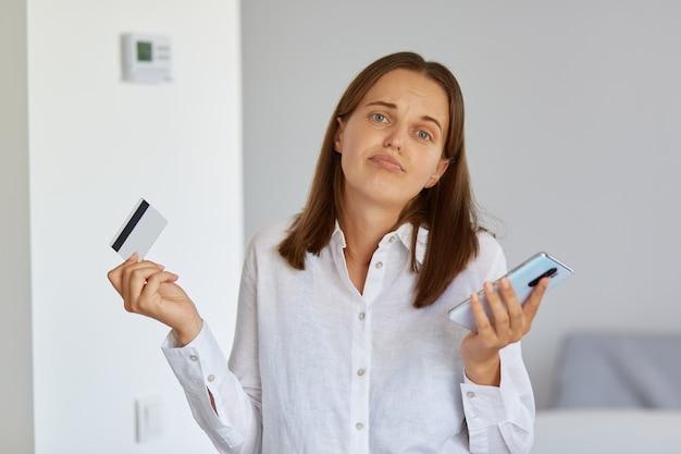 Portret van een verbaasde vrouw met donker haar die met mobiele telefoon en creditcard in handen staat, schouders ophaalt, weet niet hoe al het geld van haar bankkaart is uitgegeven.