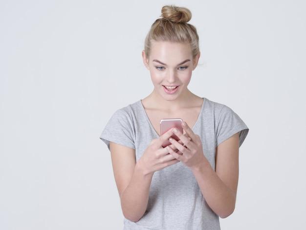 Portret van een verbaasde vrouw met mobiele telefoon in handen - in de studio