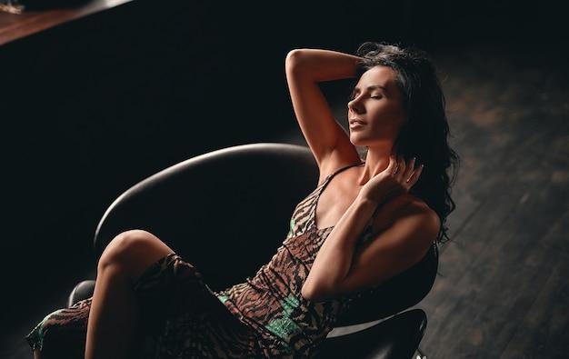 Portret van een verbluffende mooie brunette, gekleed in een jurk die in een fauteuil zit en poseert, haar lange krullende haar rechttrekken met haar handen.
