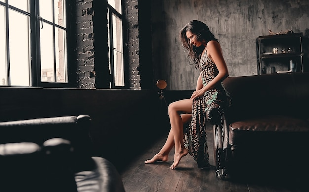 Portret van een verbluffende mooie brunette met krullend haar, gekleed in een jurk die op een leren bank zit en poseert, met lange slanke benen.