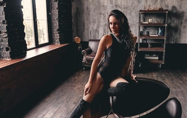 Portret van een verbluffende mooie brunette met krullend haar in een zwart zwempak uit één stuk, in suède hoge laarzen en mesh panty's, die poseert op een fauteuil met lange slanke benen.