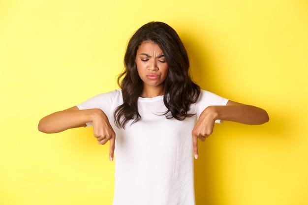 Portret van een verdrietig en teleurgesteld afro-amerikaans meisje, klagend over iets ergs, kijkend en wijzend met de vingers naar beneden met een ontevreden gezicht, staande over een gele achtergrond