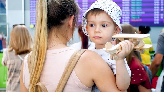 Portret van een verdrietig jongetje dat moeder op de luchthaven knuffelt en speelgoedvliegtuig vasthoudt.