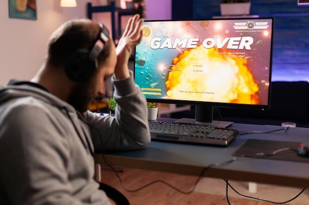 Portret van een verdrietige, overstuur gamer die een space shooter-videogame verliest. verslagen man met koptelefoon die online cyber streamt tijdens gametoernooien met behulp van draadloos technologienetwerk