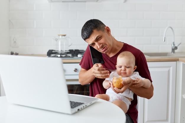 Portret van een verdrietige, overstuur man met een kastanjebruin casual t-shirt zittend met dochtertje of zoon op de knieën, pratend over de telefoon en huilend, heeft werk nodig en zorgt voor de baby, heeft geen tijd.