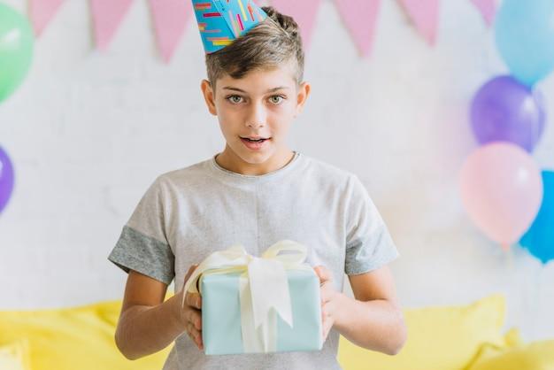 Portret van een verjaardagscadeau van de jongensholding Gratis Foto