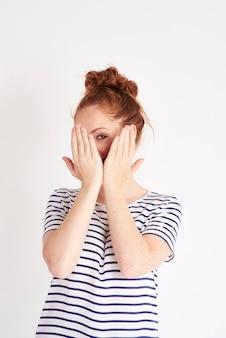 Portret van een verlegen vrouw die gezicht bedekt met handen geschoten